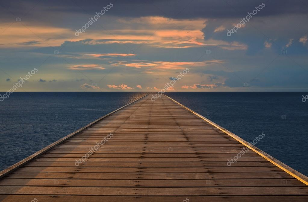 Old wood bridge to the sea with cloudy sky