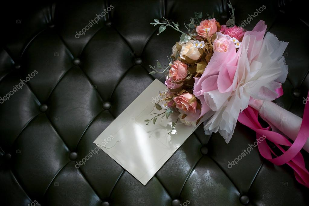 Envelope card and flower bouquet on dark green leather background ...