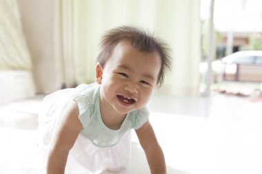 Face of asian baby 10 month aged crawling in living room