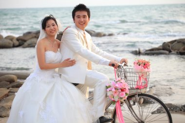 Couple of young man and woman in wedding suit ridiing old bicycle