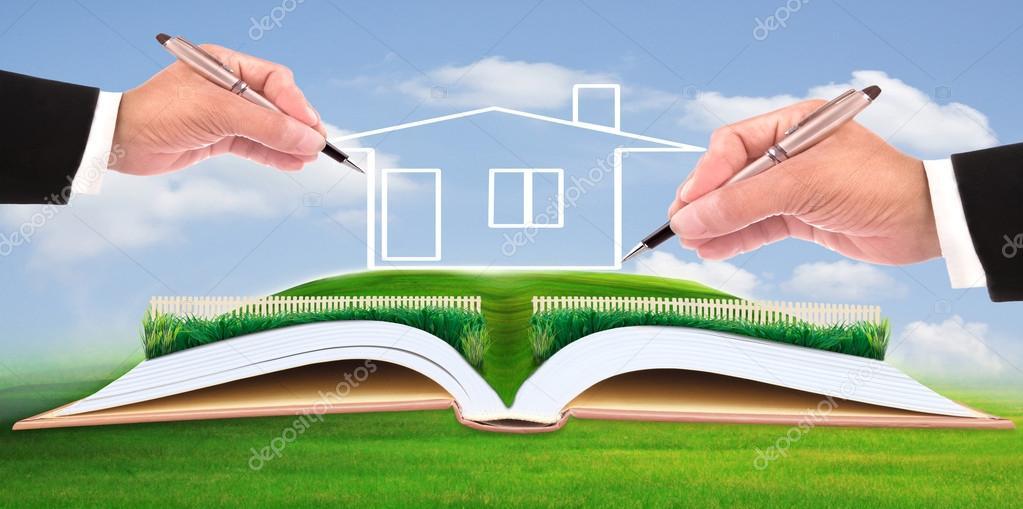 business man writing new house on beautiful green field