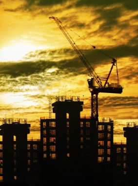 Silhouette of crane and building construction and sun set sky wi
