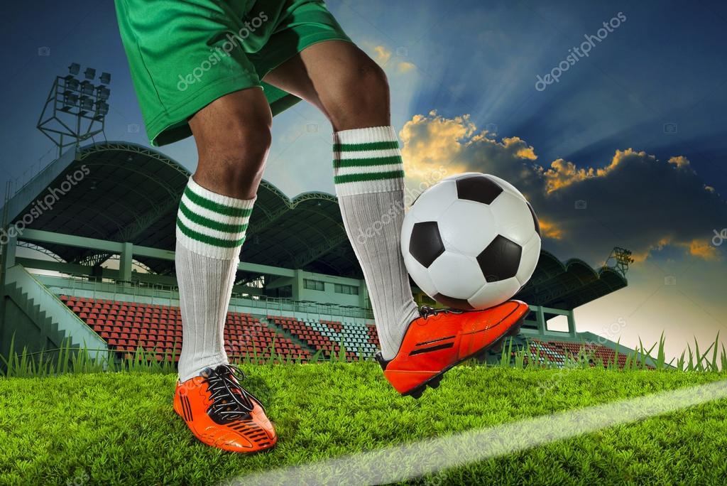 Jugador de la bola de pie sosteniendo el balón el tobillo ...
