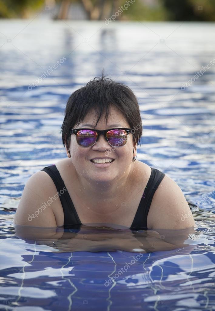 e1fe64384d Mollig Frau Badeanzug tragen und liegen in Warmwasserbecken mit entspannten  Gesicht für gute gesunde Pflege Fette Sonnenbrille tragen — Foto von ...