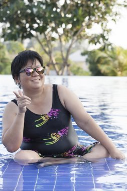 chubby woman wearing swimming suit and  wearing sun glasses with