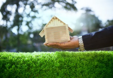 Hand of business man and wood house model on beautiful green gra