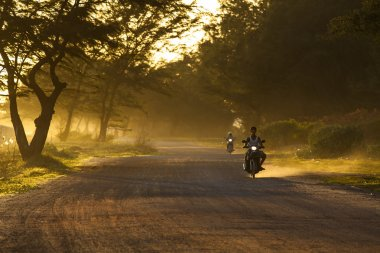 RAYONG THAILAND-AUGUST 11 : unidentified people riding motorcycle along dusty road in undevelopment rural district of Rayong province eastern of thailand on august11,2014 in RayongThailand