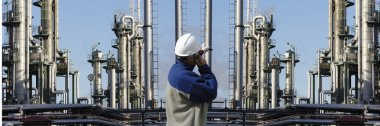oil worker pointing at giant oil and gas industry
