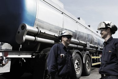 Oil workers re-fueling large truck