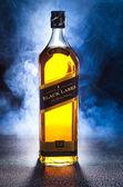 whisky Johnnie walker s kouře na černém pozadí