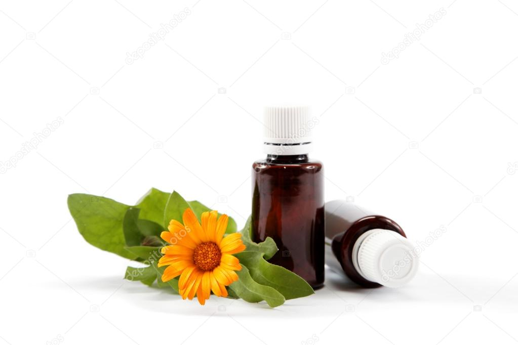 Medications and marigold flower isolated on white background.