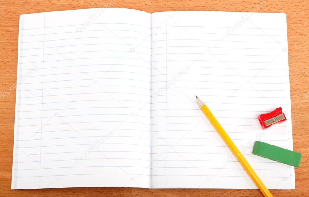 An opened notebook, pencil and stationery on a wooden table.