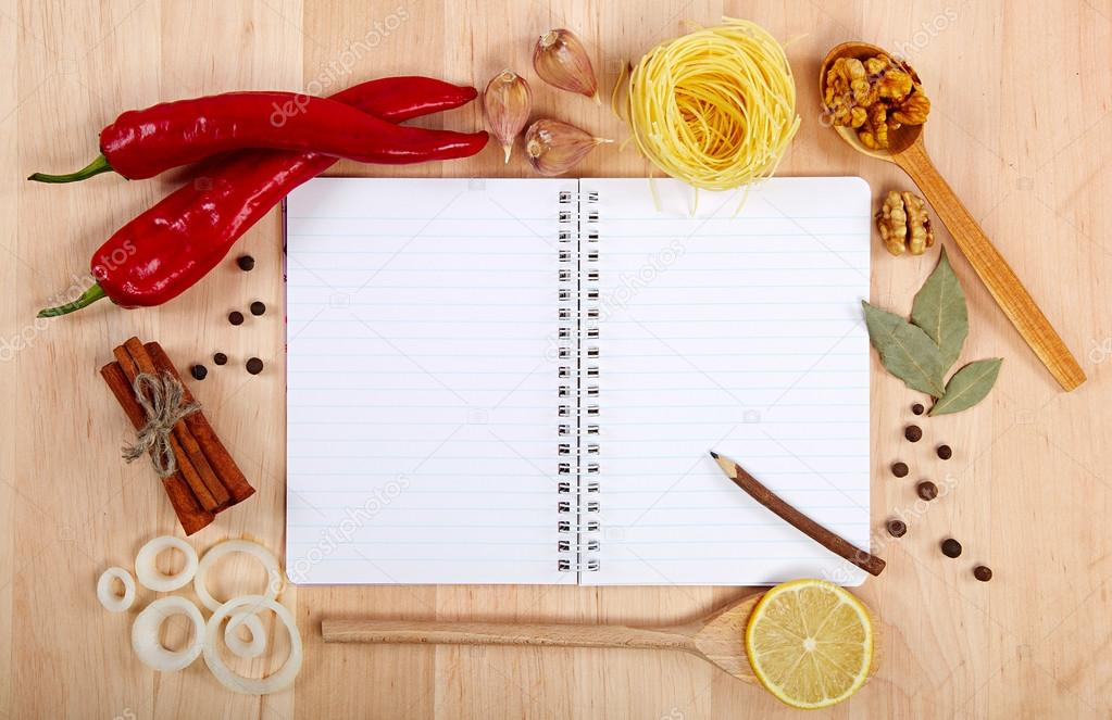 Notebook for recipes, vegetables and spices on wooden table.