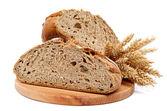 Dvě poloviny pecen žitného chleba a uši pšenice