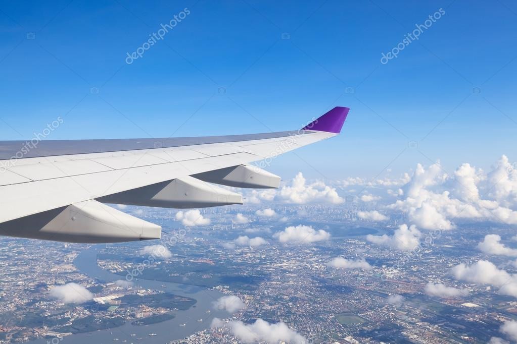 Wing of an airplane flying above the clouds. people looks at the