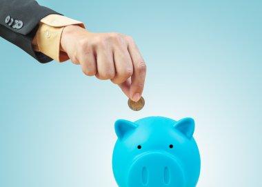 Saving money, hand putting coin into piggy bank