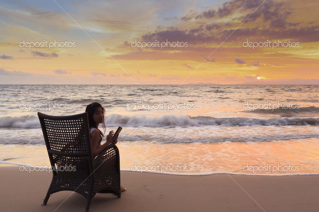Happy Woman Holding Digital Tablet and Smiling at sunset
