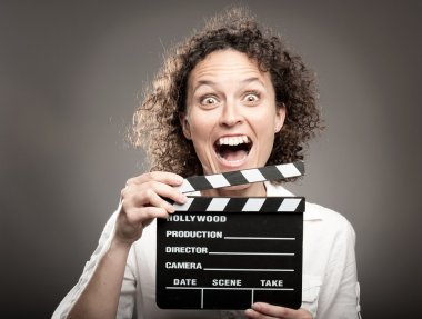 Business woman holding a movie clapper board on a grey background stock vector