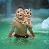 Fotografia bambini asiatici felici divertendosi in piscina