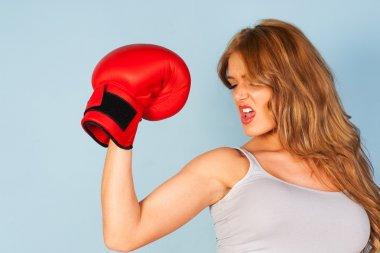Beautiful woman flexing arm muscles wearing a boxing glove