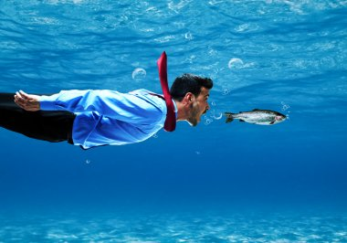 Funny businessman swimming underwater