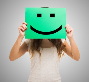 Woman holding a smiling emoticon