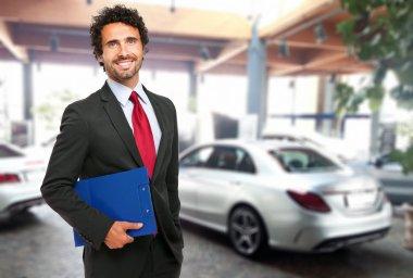 Handsome smiling car dealer