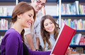Fotografie studenti čtení knihy v knihovně