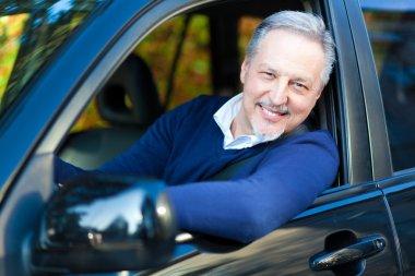 Mature man driving his car