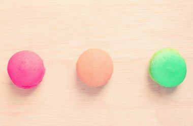 Sweet colorful macaroons on wood with retro filter effect stock vector