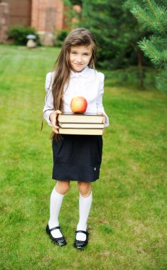 Young girl in school uniform with stack of books