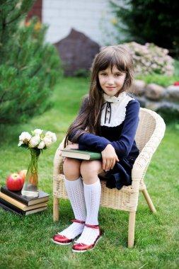 Cute girl in school uniform holding a book