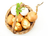 Photo Wicker basket with colored eggs onion and parsley  isolated