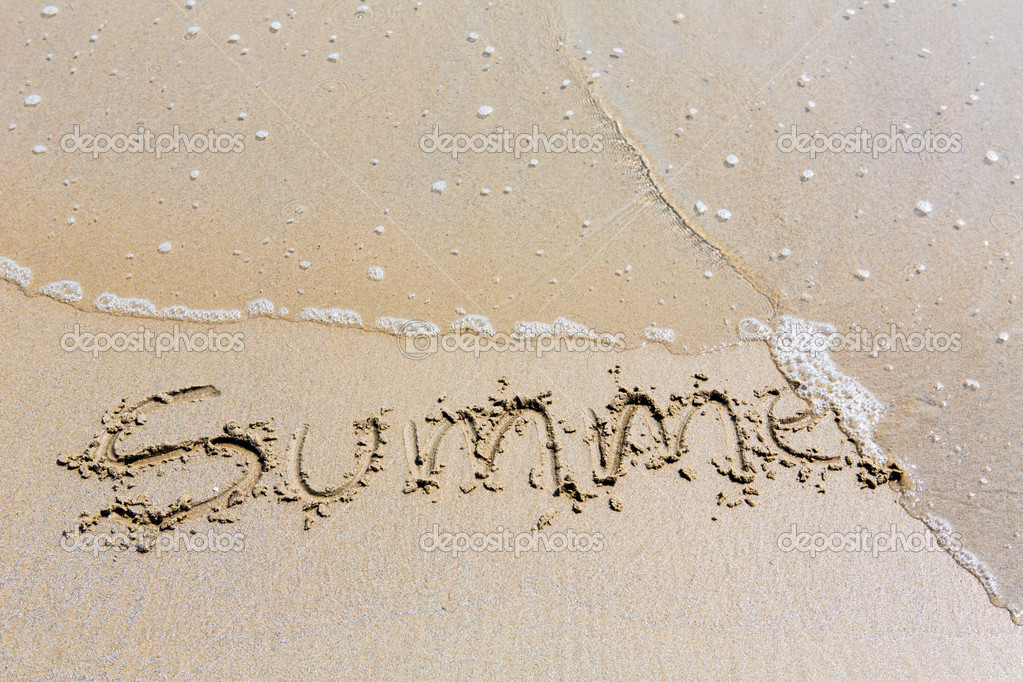 Summer handwritten inscription in sand on a beach