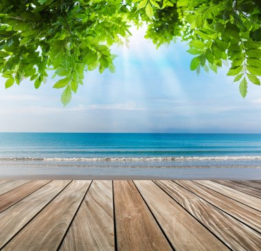 wood terrace on the beach with green leaf and sun light