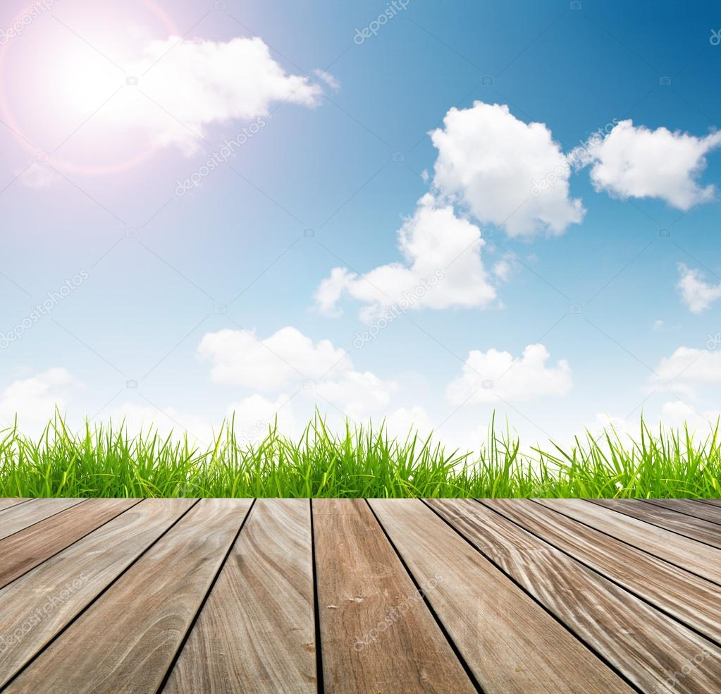 Fresh spring green grass with blue sky and wooden floor with sun