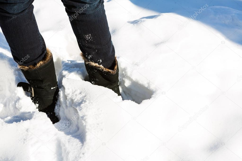 Woman legs in winter boots on snow