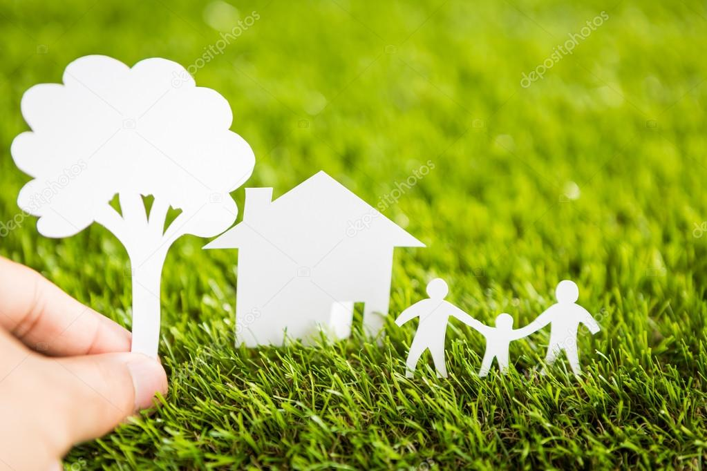 Paper cut of family with house and tree on fresh spring green gr