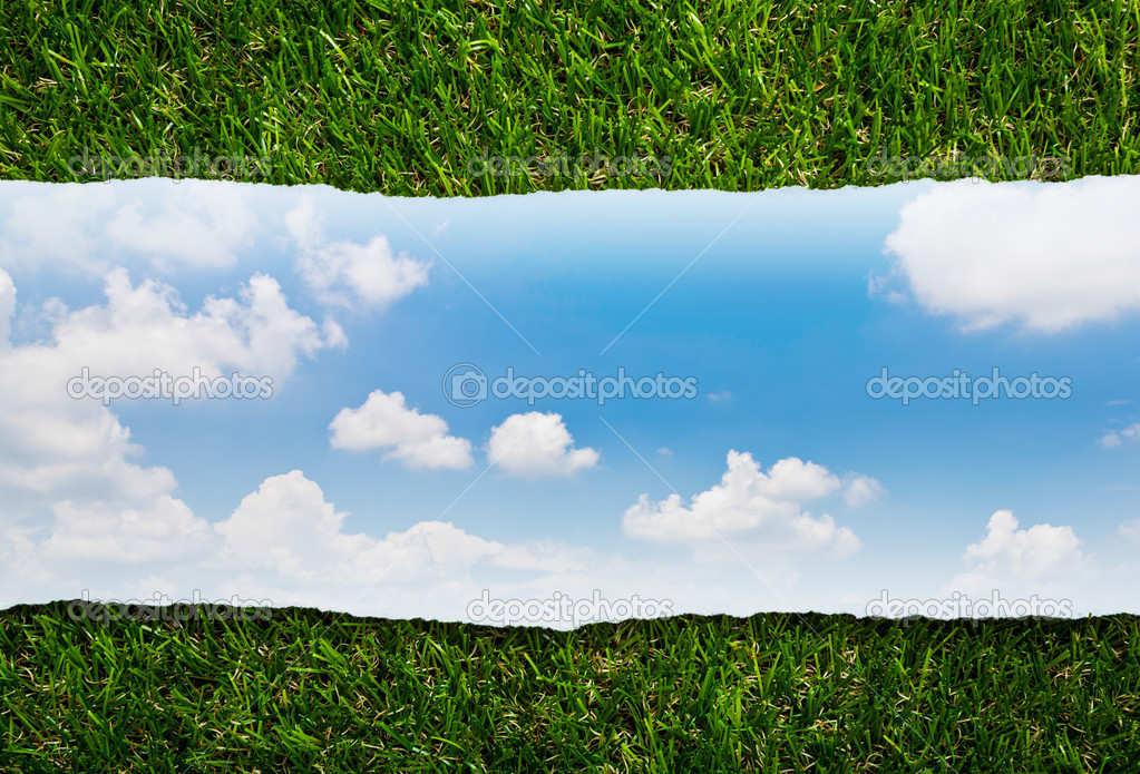 Ripped paper on green grass and blue sky