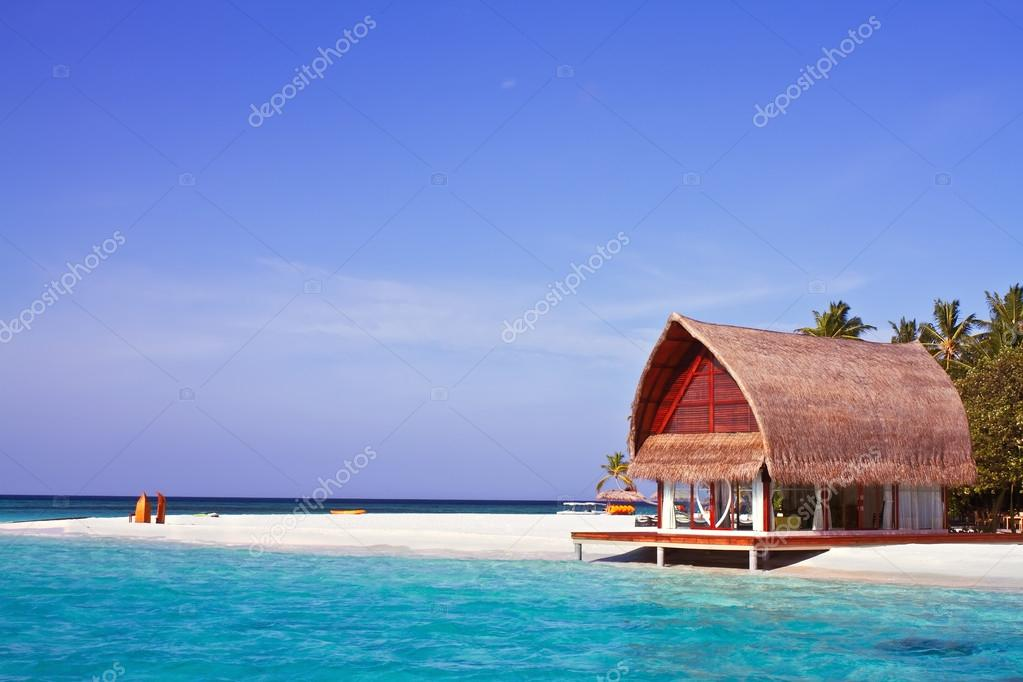 Landscape photo of beach house in Maldive ocean with blue sky