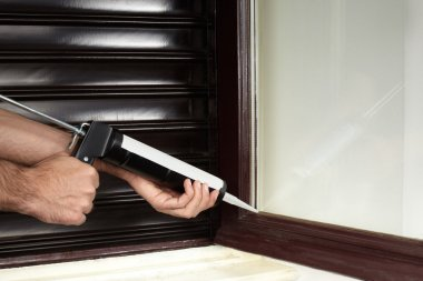 Applying silicone on window with caulking gun tool