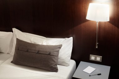 Modern bedroom, pillow and lamp at night