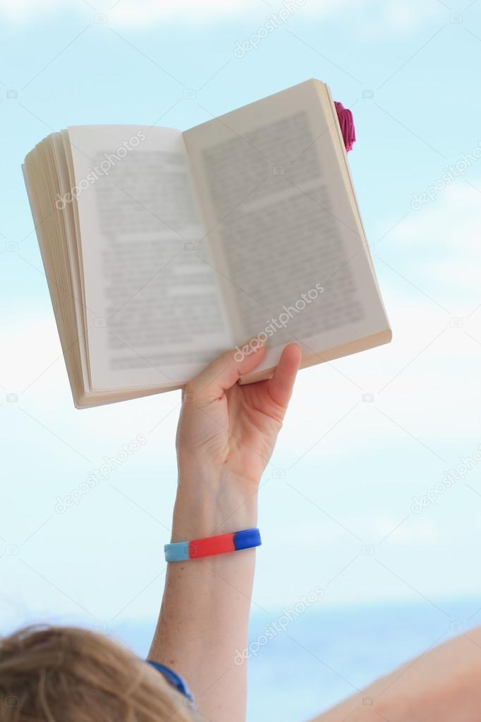 hand holding book over blue sky