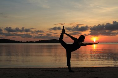 Silhouette of a yoga girl at sunrise
