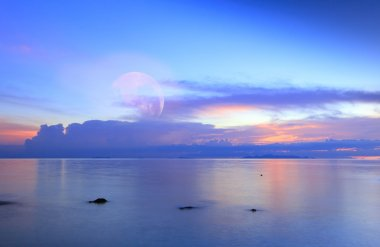 Full moon over blue sea and sky