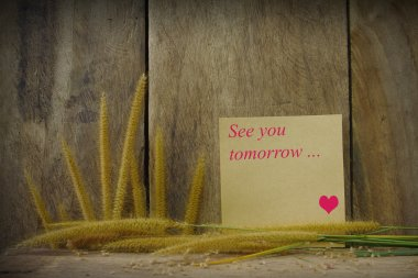 Still life with see you word wrote on notepad and foxtail grass