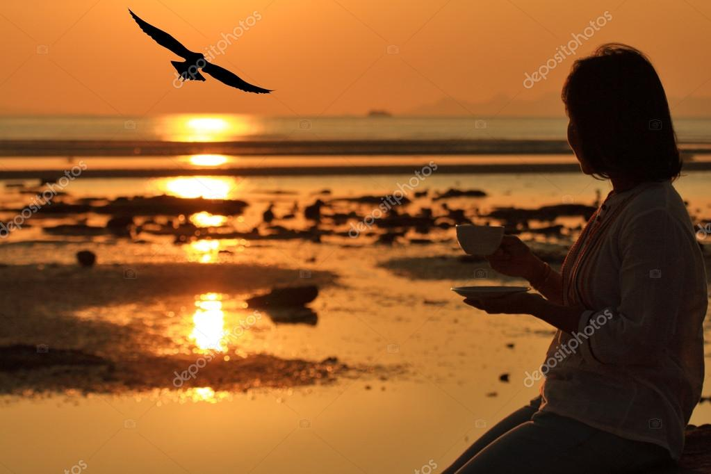Silhouette woman holding coffee looking at seagull flys over seascape sunset