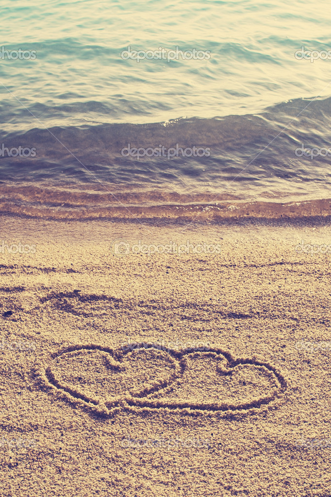 Heart shape icon  drawn on beach sand  in vintage style