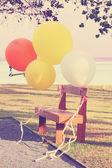 Fotografie barevné balónky a dřevěné židle