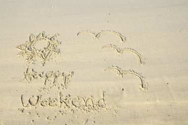 Happy weekend wrote on sand